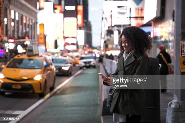waiting for the taxi in times square new york - car pooling stock photos and pictures