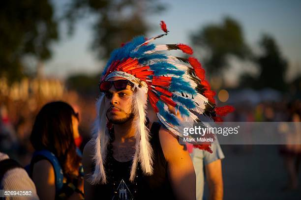 Waiting in line for a drink, Jermaine Blum wears a Native American headdress during the Governors Ball Music Festival on Randall's Island in New...