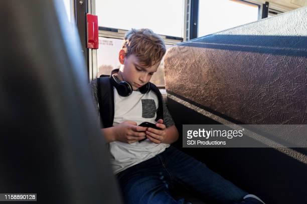 バスで待って、十代の少年はスマートフォンでゲームをプレイ - 乗り物に乗って ストックフォトと画像