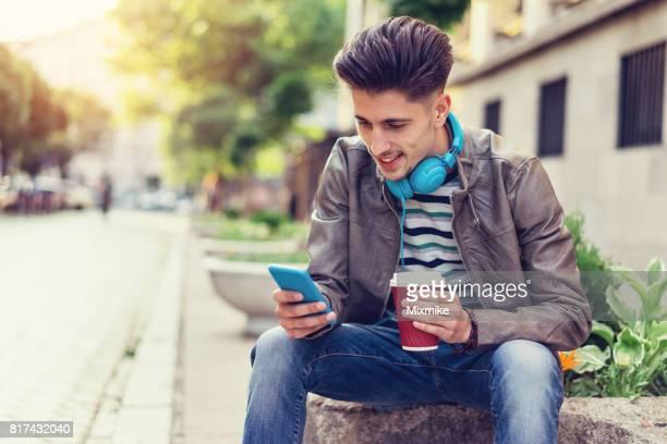 Wachten op de straat met koffie en mobiel praatje