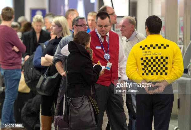 Waiting passengers being assisted by airport employees one of whom wears a sweater that reads 'Terminal Follow Me' at the airport in Frankfurt am...