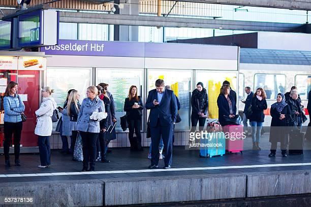 Passagiere warten in Bahnhof Düsseldorf