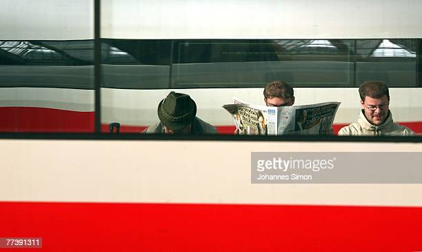 Waiting passengers of the German rail carrier Deutsche Bahn reading newspapers are reflected in the window of an ICE train at Hauptbahnhof Main...