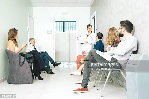 Wartezimmer, reife Ärztin im Gespräch mit einem Patienten