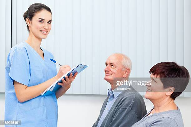 waiting room - nurse filling form - medical receptionist uniforms stock photos and pictures