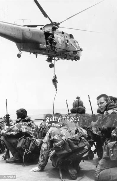 Waiting to be lifted by a Westland Sea King helicopter, Royal Marines from 40 Commando crouch on the flight deck of HMS Hermes, which heads the naval...