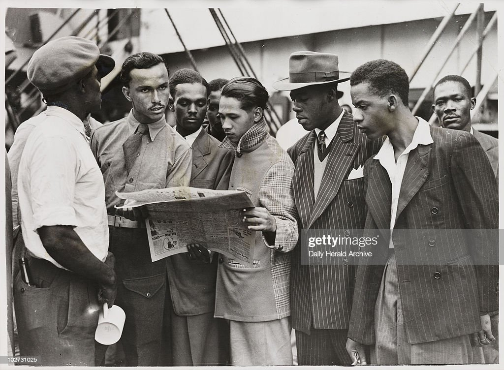 Waiting to disembark from the 'Empire Windrush', 21 June 1948. A photograph of passengers reading a newspaper whilst waiting to disembark from the 'Empire Windrush', having sailed from Jamaica, taken by an unknown photographer for the Daily Herald newspaper. During the war, thousands of men and women from the Caribbean had served in the armed forces. When the 'Empire Windrush' stopped in Jamaica to pick up servicemen, many people, having seen the 'Daily Gleaner' newspaper advertising the journey for £28.10, decided to travel to Britain. On 24 May the ship left Kingston, Jamaica with nearly 500 passengers. It docked at Tilbury on 21 June 1948.