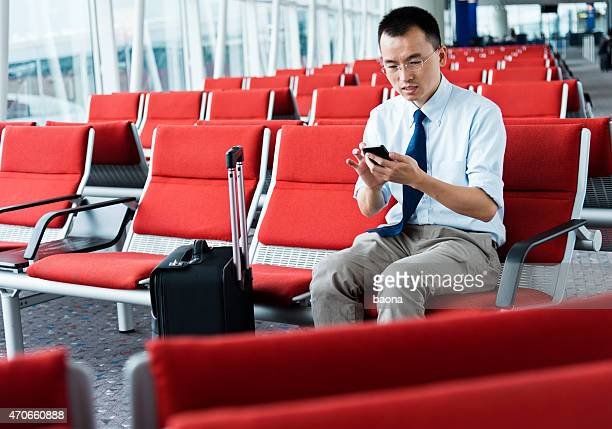 waiting traveller using mobile phone