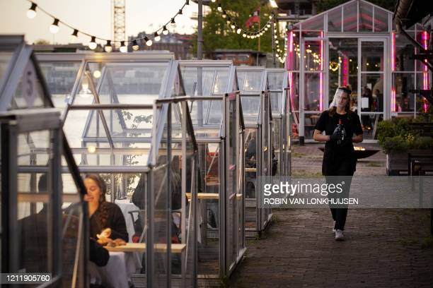 A waitres wearing a protective faceshield arrives to serve wine to friends having dinner in a socalled quarantine greenhouses in Amsterdam on May 5...