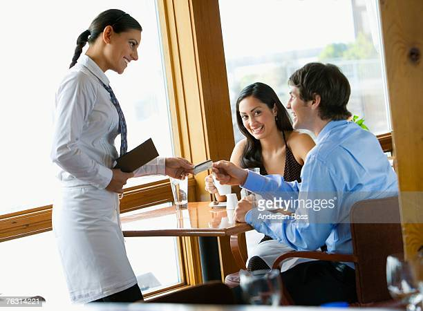 Waitress accepting credit card from young couple in restaurant