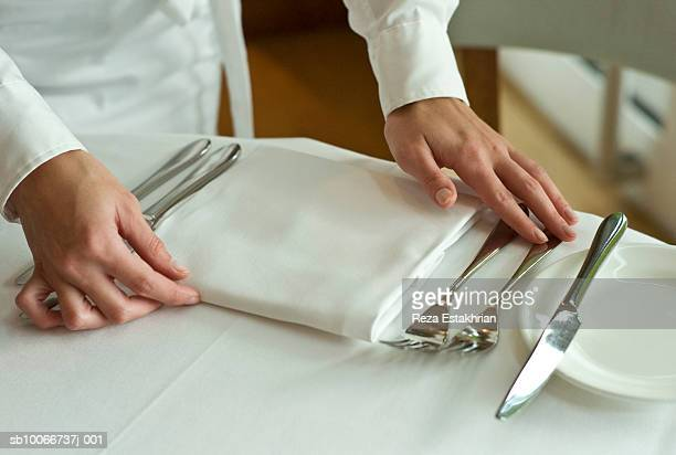 waitress adjusting table settings in restaurant, mid section - テーブルナプキン ストックフォトと画像
