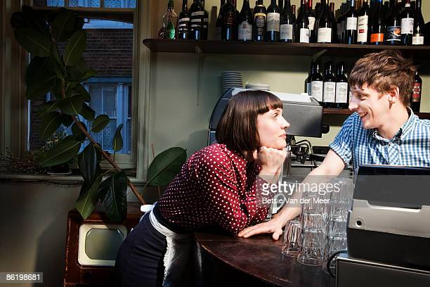 waitress and barman flirting in restaurant. - flirting stock pictures, royalty-free photos & images