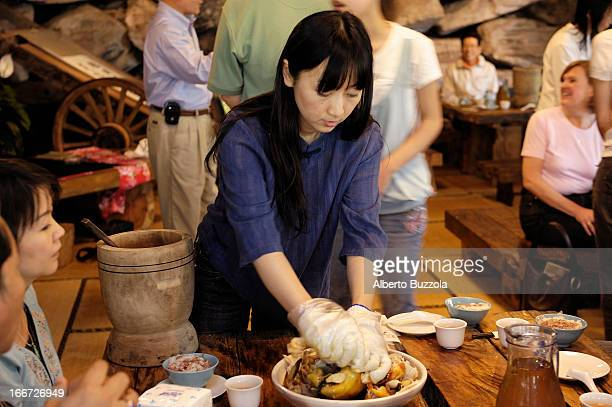"""Waitress at a Hakka's restaurants """"carving"""" a duck in the traditional Hakka way, with her hands instead of a knife.."""