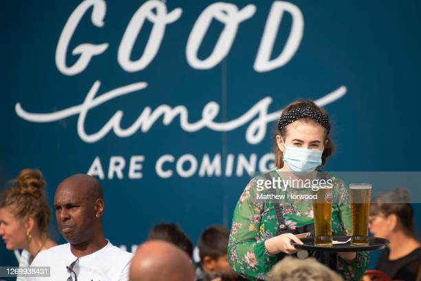 Waitress at a restaurant carries a tray of alcohol on August 31, 2020 in Cardiff, Wales. More thank 60m discounted meals have been served under the...