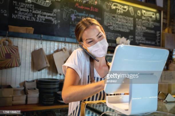 serveuse dans un restaurant obtenant une commande de livraison au téléphone et portant un masque facial - restaurant photos et images de collection