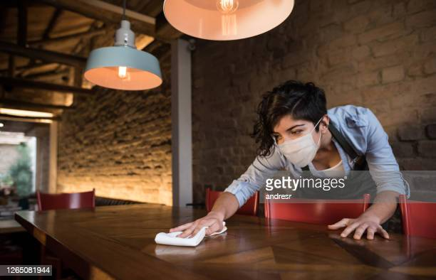 waitress at a restaurant wearing a facemask and cleaning the tables - biosecurity stock pictures, royalty-free photos & images