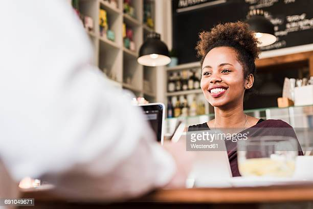 Waitress at counter in a cafe smiling at customer