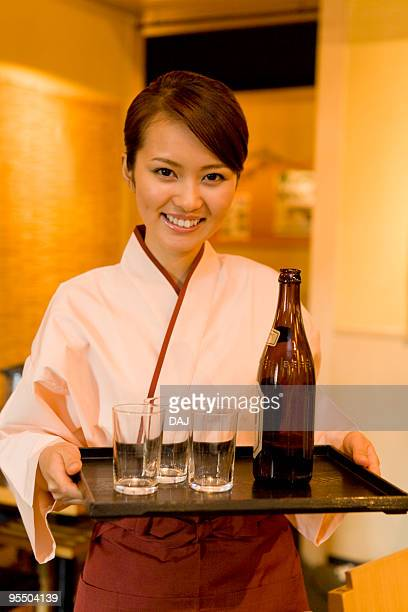 A Waitress Bringing a Beer Bottle and Glasses