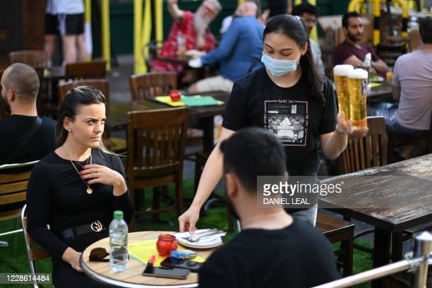 Waitress brings drinks to a couple outside a cafe in Soho, in London on September 20, 2020 as the British government consider fresh nationwide...