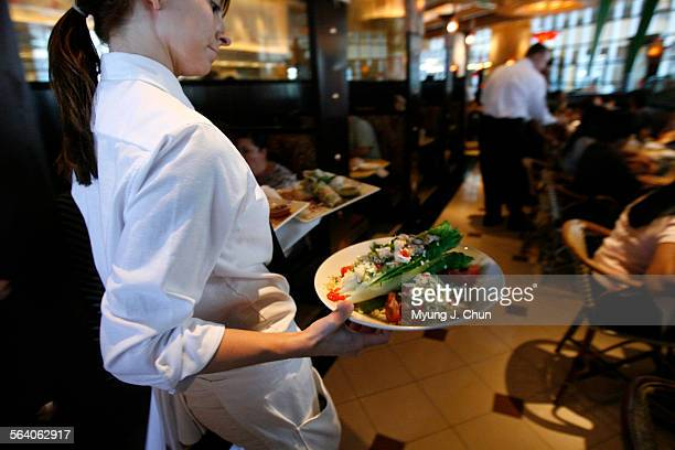 A waitress carries an armful of food during lunchtime at the Cheesecake Factory in Sherman Oaks on Friday July 28 2006 High gas prices have caused...