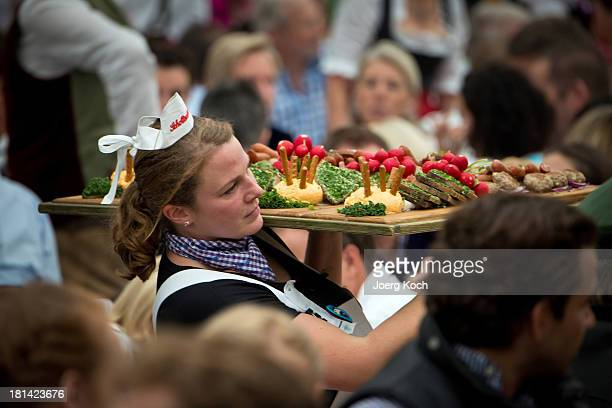 A waitress carries Bavarian food at the Oktoberfest 2013 beer festival at the Schottenhameltent at Theresienwiese on September 21 2013 in Munich...