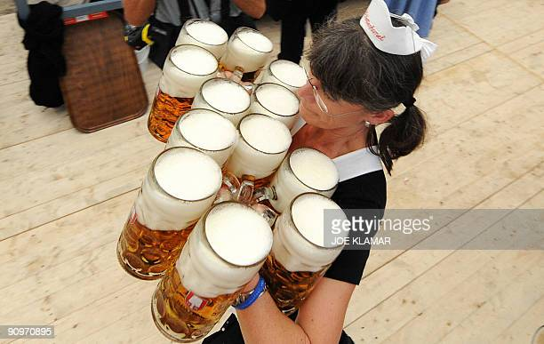 A waitress carries beer during the Oktoberfest beer festival on September 19 2009 at the 'Theresienwiese' in Munich southern Germany The world famous...