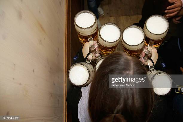 A waitress carries beer mugs after the kick off of the 2016 Oktoberfest beer festival in the Hofbraeu tent at Theresienwiese on September 17 2016 in...