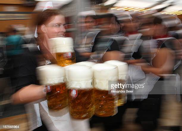 A waitress carries beer mugs at a beer tent during the opening day of the Oktoberfest 2012 beer festival at Theresienwiese on September 22 2012 in...