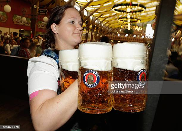 A waitress carries beer mugs at the Paulaner beer tent on the opening day of the 2015 Oktoberfest on September 19 2015 in Munich Germany The 182nd...