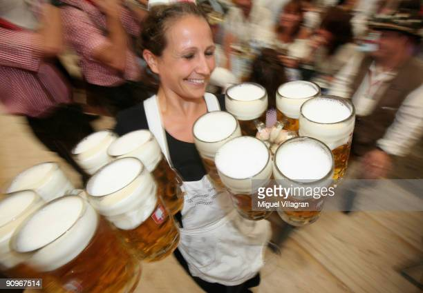 A waitress carries beer mugs at the Schottenhamel beer tent on September 19 2009 in Munich Germany Oktoberfest is Germany's and the world largest...