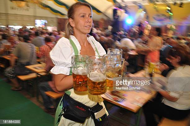 A waitress carries beer mugs during the 'Wiener Wirten Tag' as part of Wiener Wiesn Festival 2013 on September 25 2013 in Vienna Austria
