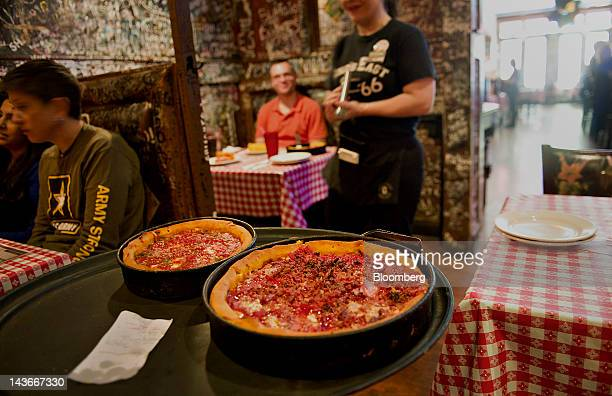 A waitress carries deep dish pizzas to customers at Gino's East restaurant in Chicago Illinois US on Wednesday April 18 2012 US restaurantindustry...