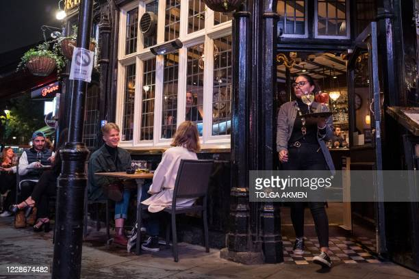 Waitress carries drinks as people drink outside a pub in Soho, in central London on September 23, 2020. - Britain on Tuesday tightened restrictions...