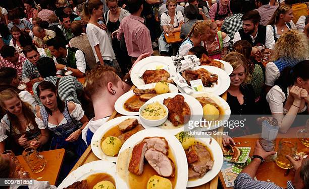 A waitress carries roast pork during day 6 of the 2016 Oktoberfest beer festival in the Hofbraeu tent at Theresienwiese on September 22 2016 in...