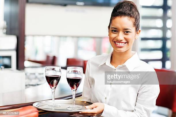 Kellnerin trägt Tablett mit Gläsern Rotwein im Restaurant