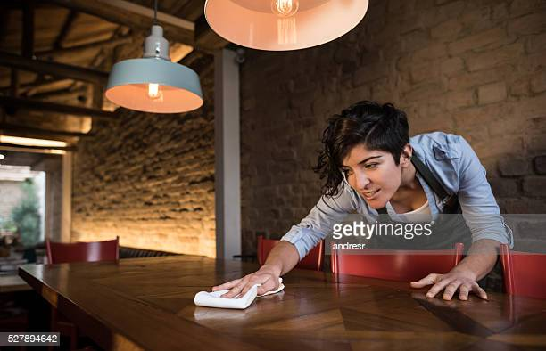 waitress cleaning a table at a restaurant - commercial cleaning stock photos and pictures