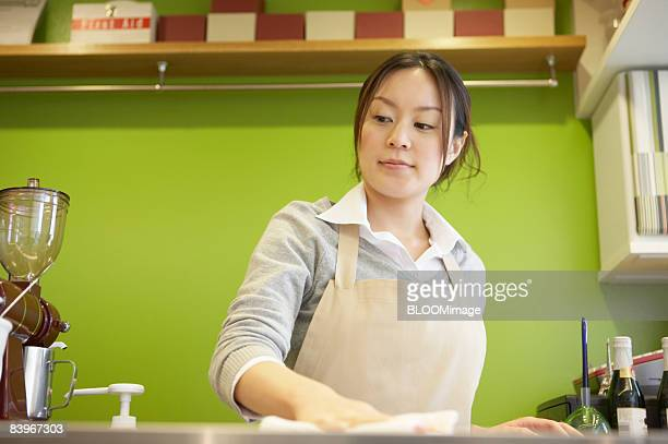 Waitress cleaning coffee bar