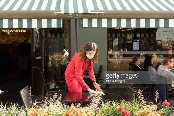 Waitress cleans a table at a restaurant bar in Soho, London. As the UK government lifted the restrictions imposed on dining services in relation to...
