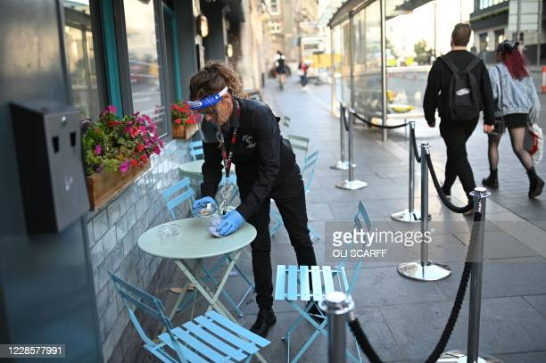 Waitress clears tables wearing full PPE in Liverpool, north-west England on September 18, 2020 after the British government imposed fresh...
