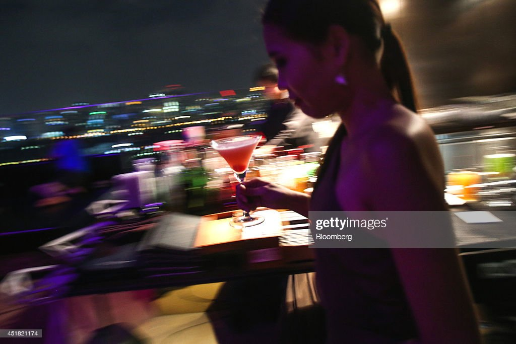 A waitress delivers a cocktail at the Park Society rooftop bar in the Sofitel So hotel, operated by Accor SA, at night in Bangkok, Thailand, on Saturday, June 28, 2014. Through a dozen coups, a tsunami, financial upheaval, floods and riots, Bangkok keeps bouncing back. With each crisis, tourism numbers slump, stocks crash and investment dips, only to return stronger than before. Photographer: Dario Pignatelli/Bloomberg via Getty Images