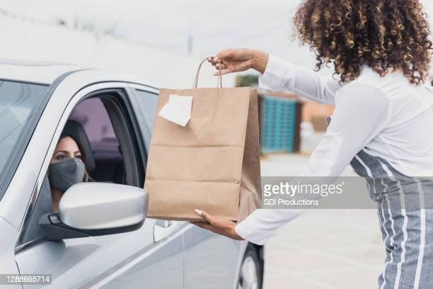 waitress delivers food to customer waiting in car - curbside pickup stock pictures, royalty-free photos & images