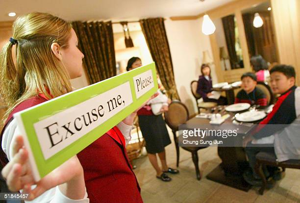 A waitress demonstrates useful phrases to South Korean students in a mock western restaurant as part of a scheme whereby students can achieve 'full...