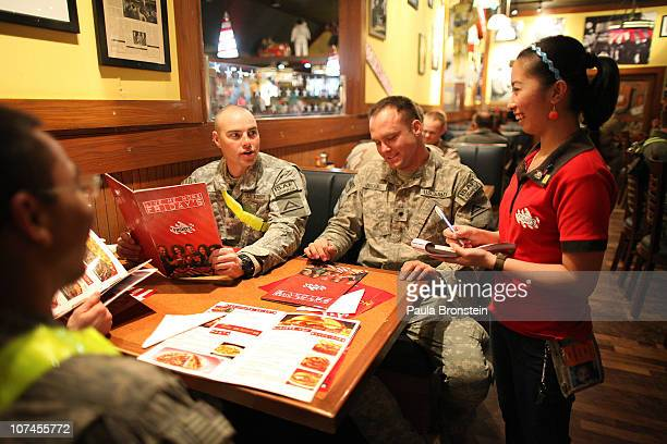 Waitress Erica Dinglasan takes a dinner order from US Army Sargent Jackie Rogers and Specialist Charles Brooks at the TGI Friday's restaurant at...