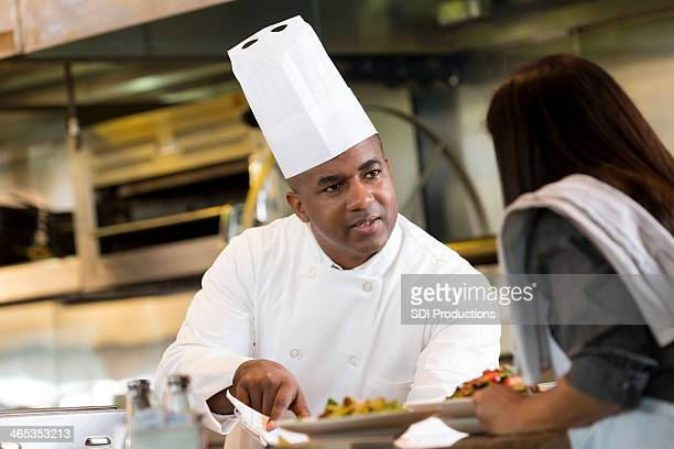 Waitress explaining customer food order to restaurant chef in kitchen