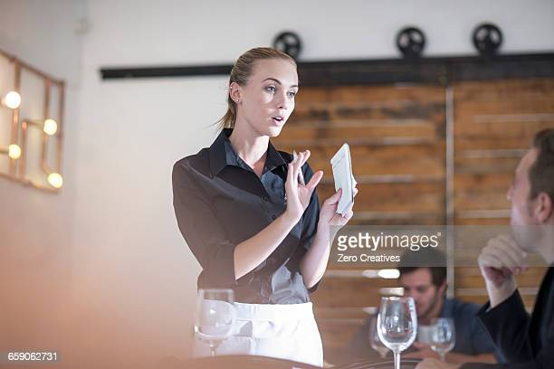 Waitress explaining to customer in restaurant