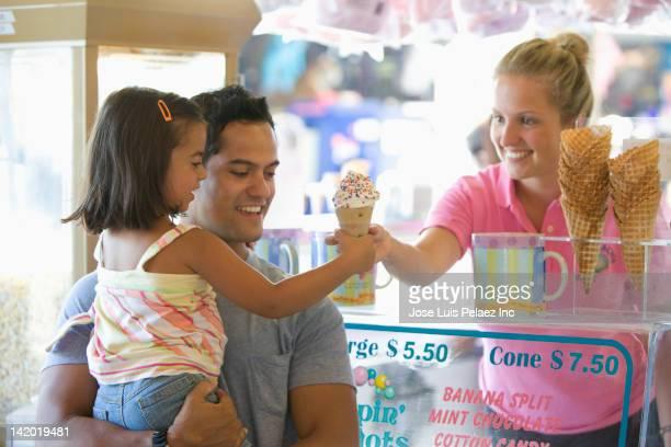 Waitress handing girl ice cream cone