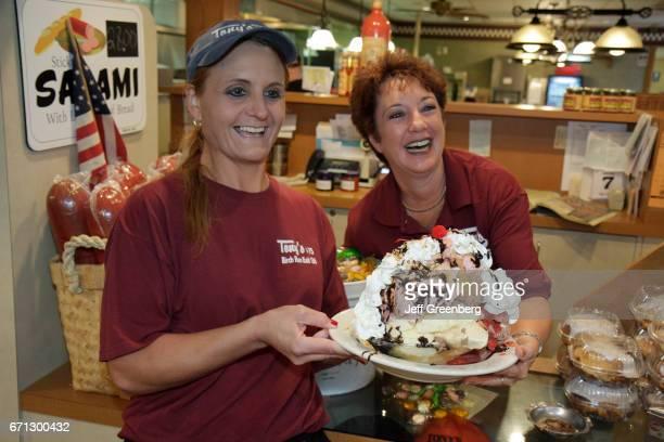 A waitress holding a huge ice cream sundae at Tony's I75 Restaurant