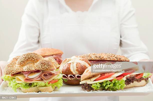 Waitress holding a tray of assorted sandwiches