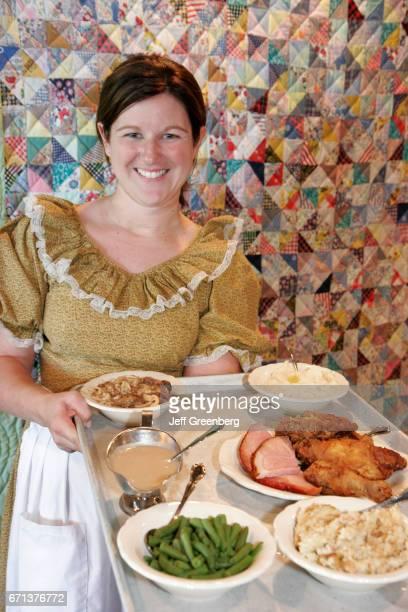 A waitress holding a tray of food at Amish Acres Historic Farm Restaurant