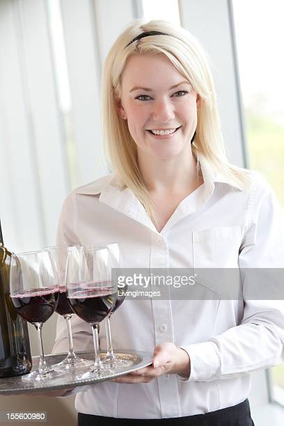 A waitress holding a tray of glasses of red wine